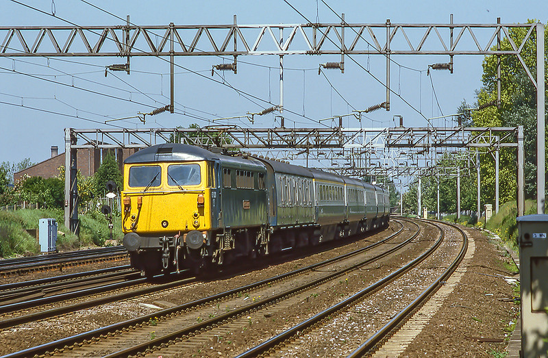 3rd Jun 1985:  87024 'Robert the Bruce' hammers south through Kenton with the 07.25 from Birmingham to Euston