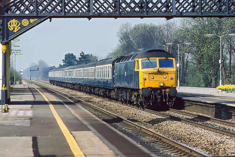 18th Apr 1985:  47615 with the 10.30 from Oxford to Paddington under the beautiful 1884 built foot bridge. at Taplow.  Very regratably this important structure could not be preserved after the new bridge was built because a cretin driving a mobile crane under  it left the jib up in the air wich pulled the  structure down.