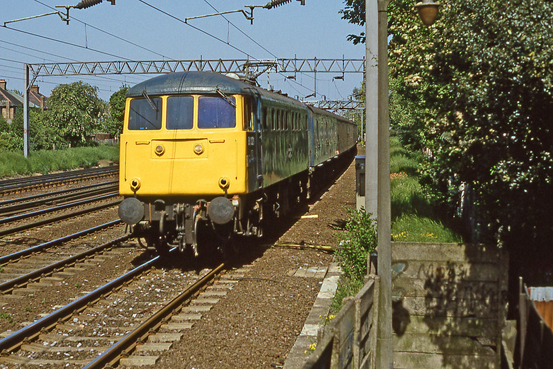 3rd Jun 1985:  In the 20 minute that I had to stay on this foot bridge in Kenton in North London I saw teo 85s. ee. line making them almost impossible to picture,.  This was the best that I could manage, 85021 is on a Parcels train.