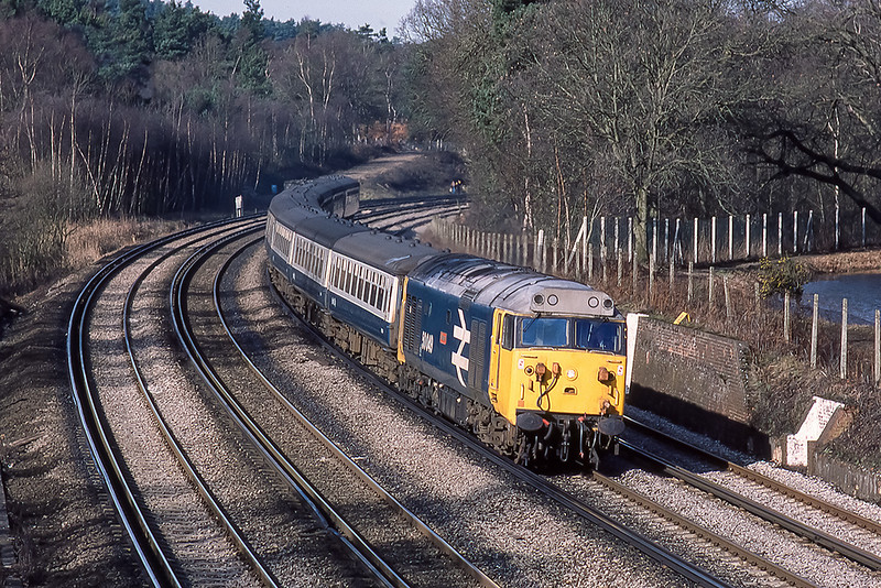 28th Mar 1985:  Rounding the curve at Pirbright is 50049 'Defiance' that is working the 05.48 from Exeter to Waterloo.  Just visible on the right is the Basingstoke canal.