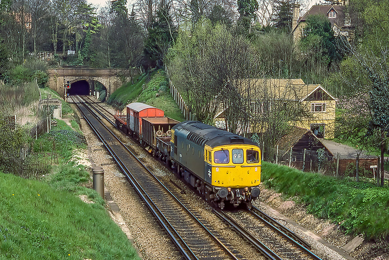 17th Apr 1985:  The sort of freight that we do not see  these days unfortunately.  Just south of Guildford station is 33024 heading south with a SpeedLink service.  Picture taken  from Ferry lane which is just in front of the second of the two tunnels in Guildford.
