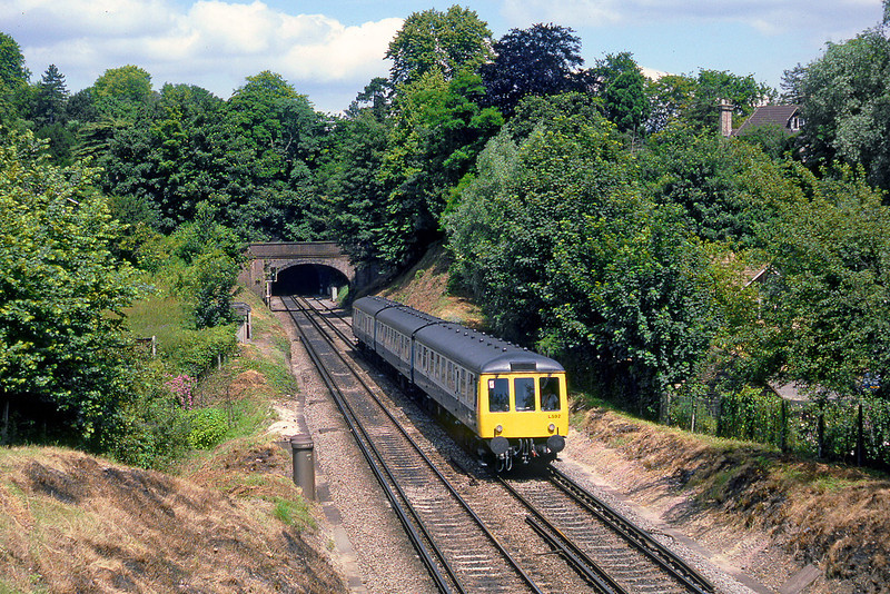 17th JUly 85:  The 11.16 from Reading to Tonbridge formed of L592 in the vale between Chalk and St Catherines Tunnels in Guildford