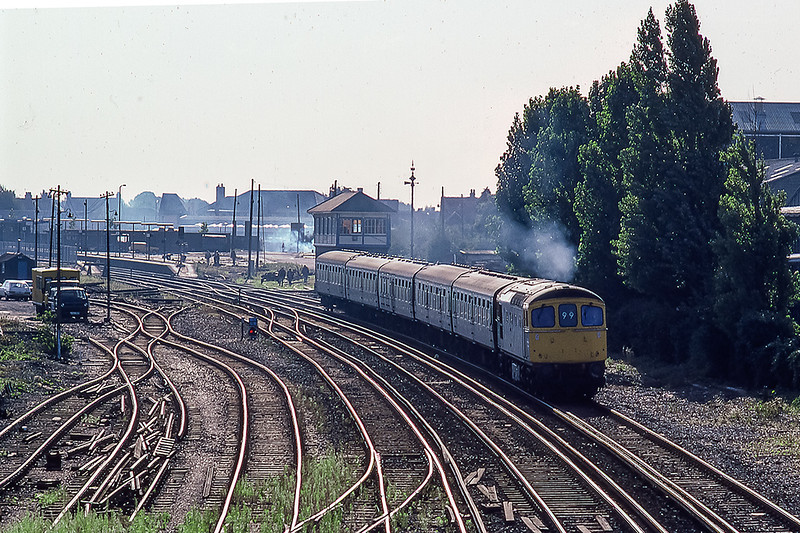 27th Aug 1986: At 09.09 33023 is departing from Chichester as it works the 08.30 from Brighton to Cardiff.  The lighting fully illustrates the considerable track layout changes that were taking place.  Bay Platform and coal yard on the  right and main goods yard to the left. In the left foreground are the remnants of the  big crossover that joined te left yard to all the running lines.