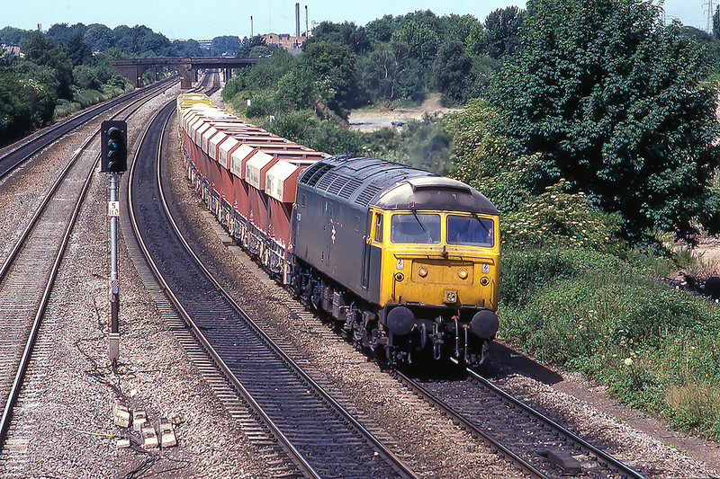 2nd Jul 1986: Passing the site of the Langley Alloys factory as it runs through Langley is  47357 with hoppers that my notes say were bound for Tilbury