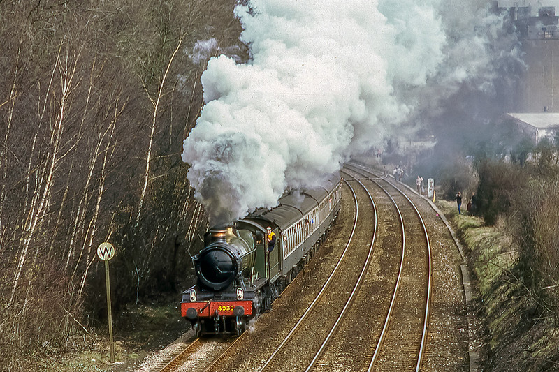 23rd Mar 1986;  On the 2nd day of the Andover Rail Event 4930 'Hagley Hall' is leaving Andover on it's way to Lugershall.  Taken from a A303 road bridge, note all the locals standing lineside