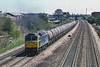 1st May v1986:  With Langley station in the distance 47033 is heading west with a rake of four wheel oil tanks.