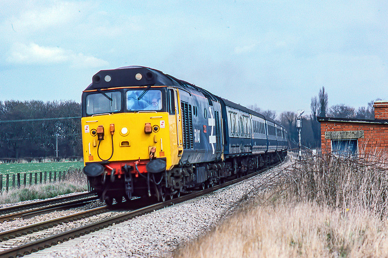 4th Apr 1986  The 13.40 Paddington to Penzance in the hand of 50047 'Swiftsure' is about to  cross the level crossing at Ufton in Berkshire.