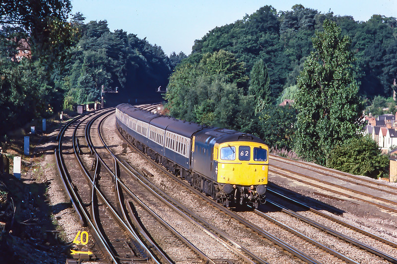 20th Aug 1986:  33002 powering the 07.16 from Salisbury to Waterloo is pictured from the foot bridge just after the Guilford line Junction.  It is hard to believe that when the original Woking station was opened the nearest house was 1 mile away in Old Woking.