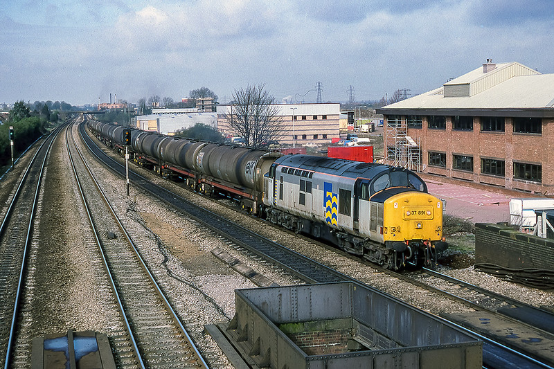 22nd Mar 1988:  Running through Langley is 37891 with a loaded oil train.  The new office complexes on the site of the old Langley Alloys are nearly completed.