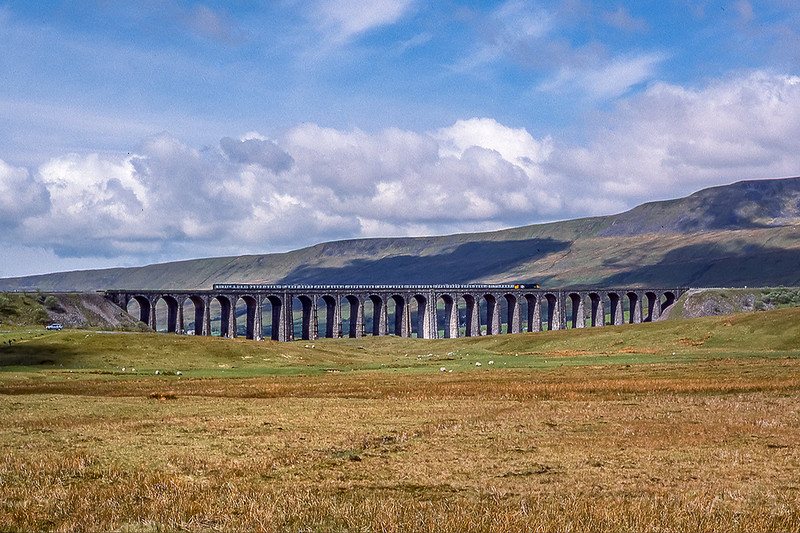 13th May 1989: A truly spectacular scene at Batty Moss  is the Ribble Head viaduct.  A 47 with 10 on heads north