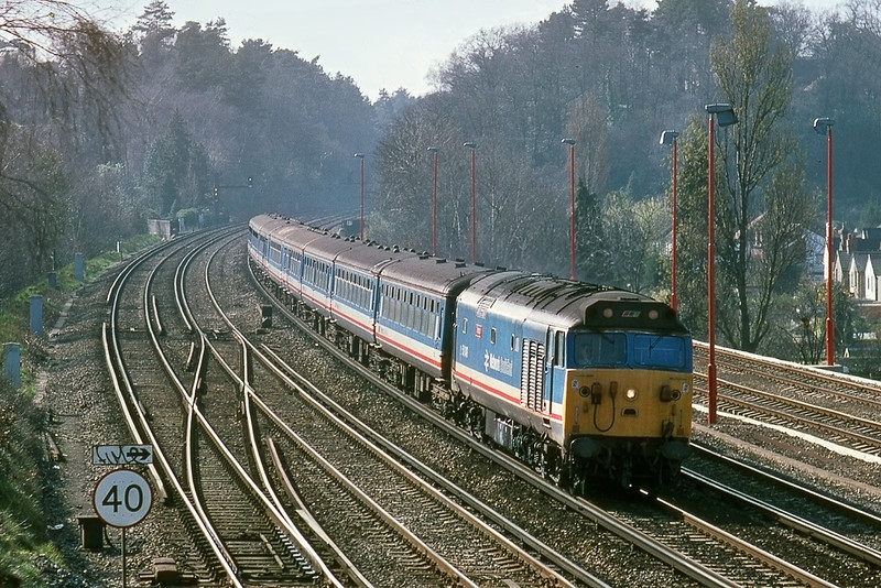12th Mar 90:  With  a matching rake of NSE stock 50049 slows for the Woking stop with an Up express from  Exeter