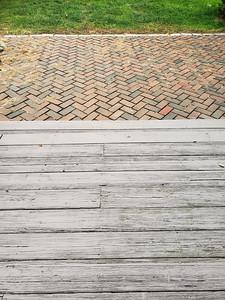 Grass, bricks, and wooden porch taken from the door.