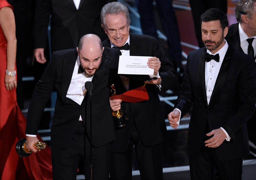 ". Jordan Horowitz, producer of ""La La Land,\"" shows the envelope revealing \""Moonlight\"" as the true winner of best picture at the Oscars on Sunday, Feb. 26, 2017, at the Dolby Theatre in Los Angeles. Presenter Warren Beatty and host Jimmy Kimmel look on from right. (Photo by Chris Pizzello/Invision/AP)"