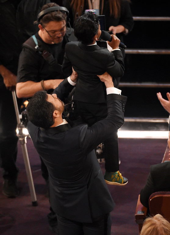 . Host Jimmy Kimmel, left, raises Sunny Pawar in the air at the Oscars on Sunday, Feb. 26, 2017, at the Dolby Theatre in Los Angeles. (Photo by Chris Pizzello/Invision/AP)