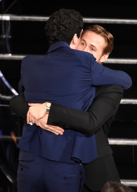""". Ryan Gosling, right, congratulates Damien Chazelle as he accepts the award for best director for \""""La La Land\"""" at the Oscars on Sunday, Feb. 26, 2017, at the Dolby Theatre in Los Angeles. (Photo by Chris Pizzello/Invision/AP)"""