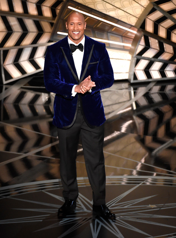 """. Dwayne Johnson introduces a performance from best original song nominee \""""How Far I\'ll Go\"""" from \""""Moana\"""" at the Oscars on Sunday, Feb. 26, 2017, at the Dolby Theatre in Los Angeles. (Photo by Chris Pizzello/Invision/AP)"""