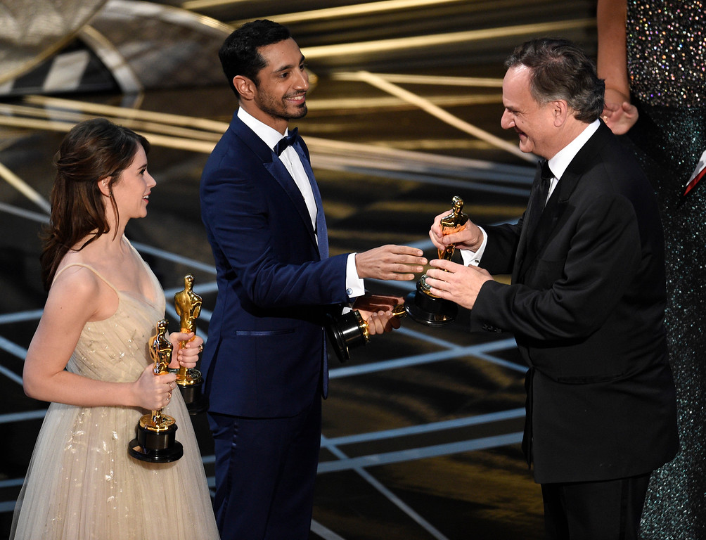 . Felicity Jones, from left, and Riz Ahmed, present Robert Legato with the award for best visual effects at the Oscars on Sunday, Feb. 26, 2017, at the Dolby Theatre in Los Angeles. (Photo by Chris Pizzello/Invision/AP)