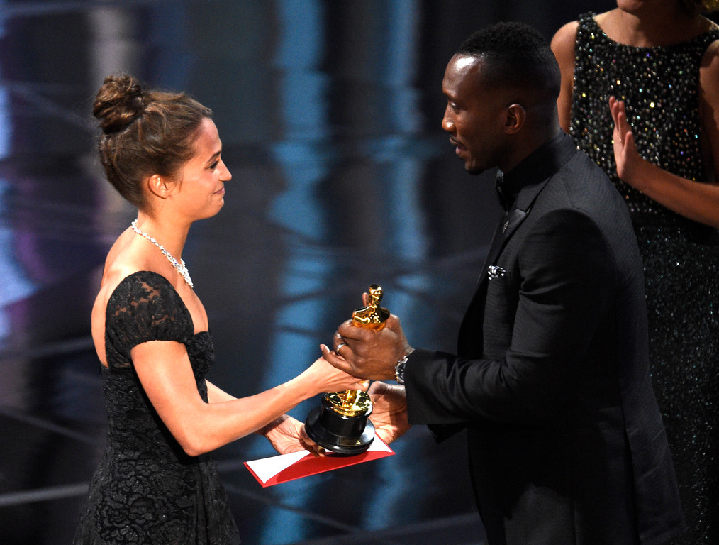 """. Alicia Vikander, left, presents Mahershala Ali with the award for best actor in a supporting role for \""""Moonlight\"""" at the Oscars on Sunday, Feb. 26, 2017, at the Dolby Theatre in Los Angeles. (Photo by Chris Pizzello/Invision/AP)"""