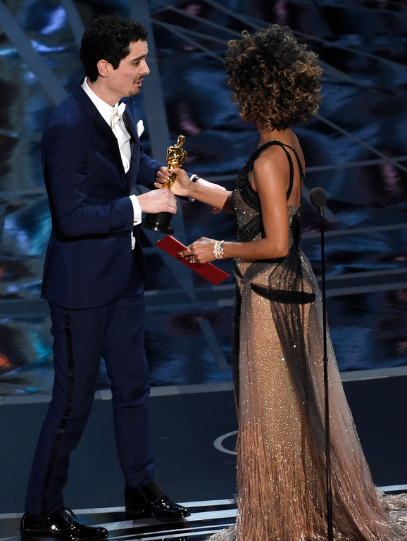 """. Halle Berry, right, presents Damien Chazelle with the award for best director for \""""La La Land\"""" at the Oscars on Sunday, Feb. 26, 2017, at the Dolby Theatre in Los Angeles. (Photo by Chris Pizzello/Invision/AP)"""