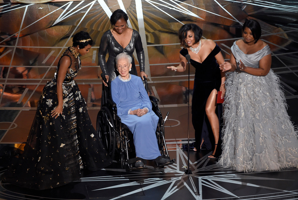 """. Janelle Monae, left, Taraji P. Henson, second right and Octavia Spencer, right, introduce Katherine Johnson, seated, the inspiration for \""""Hidden Figures,\"""" as they present the award for best documentary feature at the Oscars on Sunday, Feb. 26, 2017, at the Dolby Theatre in Los Angeles. (Photo by Chris Pizzello/Invision/AP)"""