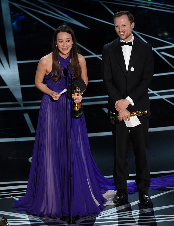 """. Joanna Natasegara, left, and Orlando von Einsiedel accept the award for best documentary short subject for \""""The White Helmets\"""" at the Oscars on Sunday, Feb. 26, 2017, at the Dolby Theatre in Los Angeles. (Photo by Chris Pizzello/Invision/AP)"""