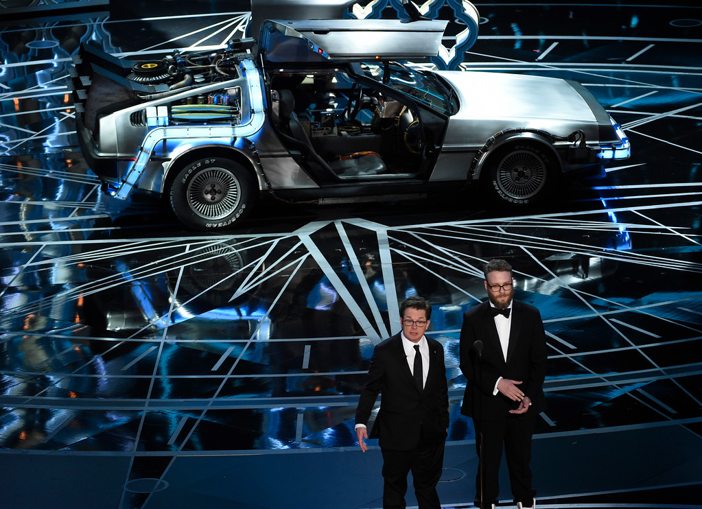 . Seth Rogen, right, and Michael J. Fox speak at the Oscars on Sunday, Feb. 26, 2017, at the Dolby Theatre in Los Angeles. Pictured on stage is a DeLorean. (Photo by Chris Pizzello/Invision/AP)