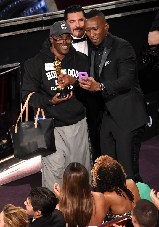 """. Mahershala Ali, right, takes a selfie with a tourist named Gary while holding his award for best actor in a supporting role for \""""Moonlight\"""" at the Oscars on Sunday, Feb. 26, 2017, at the Dolby Theatre in Los Angeles. (Photo by Chris Pizzello/Invision/AP)"""