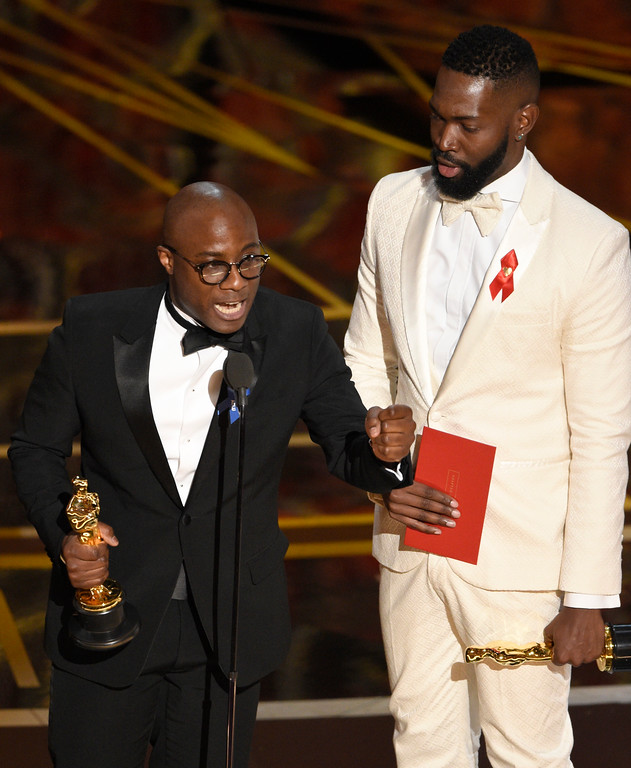 ". Barry Jenkins, left, and Tarell Alvin McCraney accept the award for best adapted screenplay for ""Moonlight\"" at the Oscars on Sunday, Feb. 26, 2017, at the Dolby Theatre in Los Angeles. (Photo by Chris Pizzello/Invision/AP)"