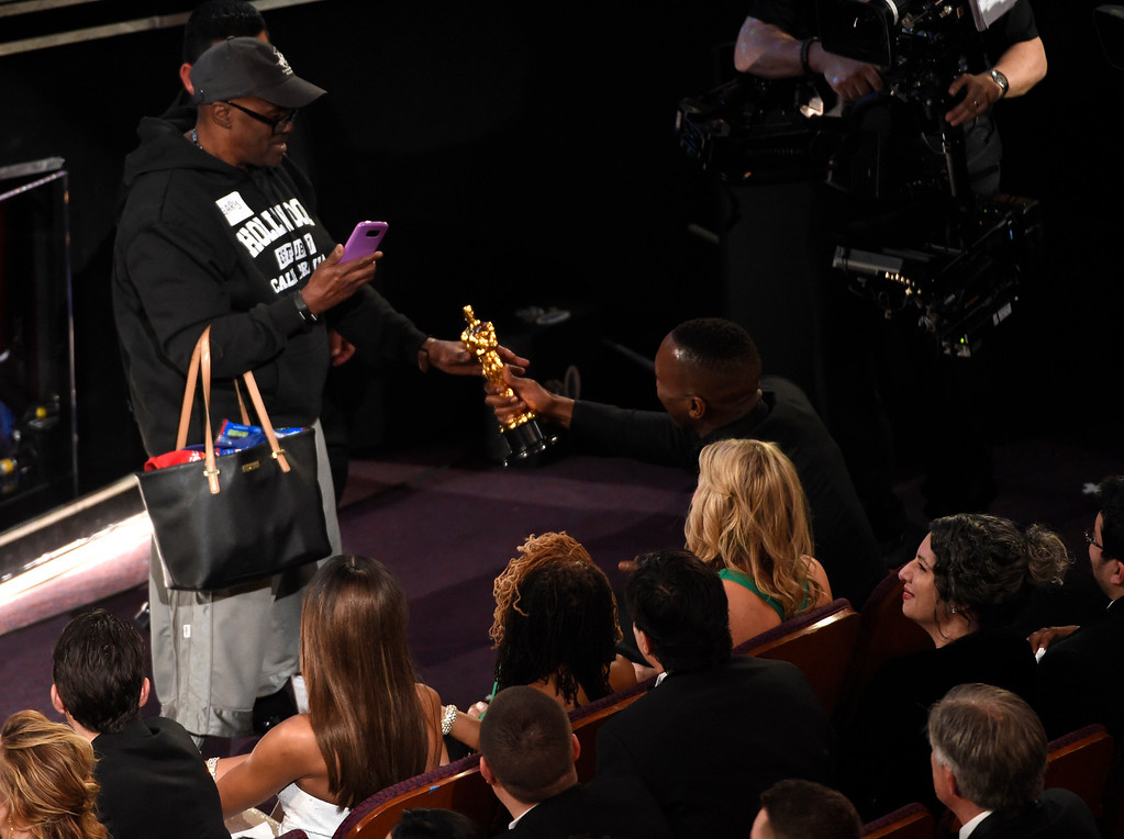 """. Mahershala Ali, right, hands his award for best actor in a supporting role for \""""Moonlight\"""" to a tourist named Gary during the Oscars on Sunday, Feb. 26, 2017, at the Dolby Theatre in Los Angeles. (Photo by Chris Pizzello/Invision/AP)"""
