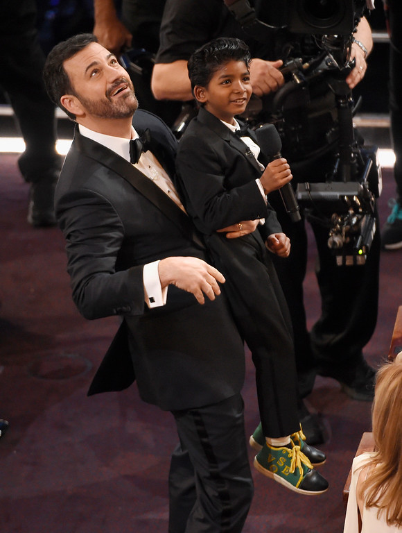 . Host Jimmy Kimmel, left, raises Sunny Pawar at the Oscars on Sunday, Feb. 26, 2017, at the Dolby Theatre in Los Angeles. (Photo by Chris Pizzello/Invision/AP)