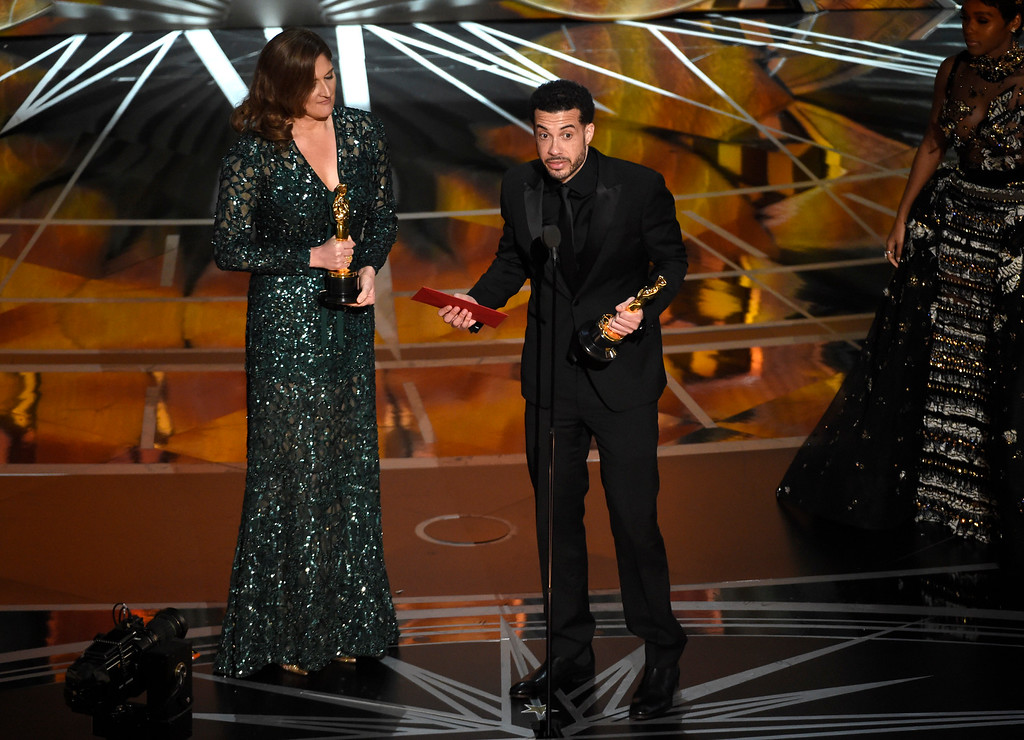 """. Ezra Edelman, right, and Caroline Waterlow accept the award for best documentary feature for \""""O.J.: Made in America\"""" at the Oscars on Sunday, Feb. 26, 2017, at the Dolby Theatre in Los Angeles. (Photo by Chris Pizzello/Invision/AP)"""
