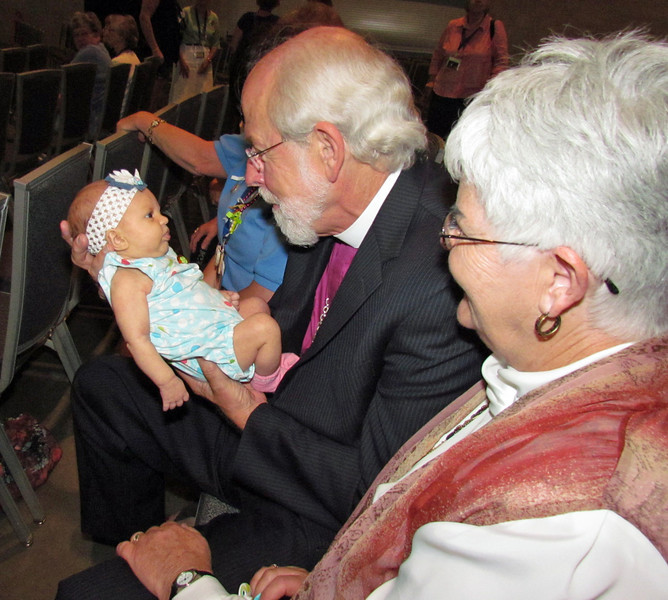 ELCA Presiding Bishop Mark Hanson holds Anna Humphrey Bruner, who is attending her first triennial gathering. Anna is granddaughter of Susan Humphrey, a former churchwide executive board member. Next to Hanson is his wife, Ione.<br /> TL