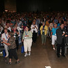 Participants gather in Jesus' name for Friday opening worship. They are clapping to the lively music.