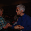 Evening prayer leader Jane Redmont (right) assists with communion at the Friday morning worship.