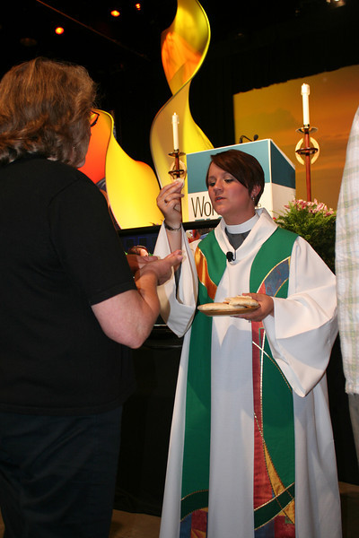 Closing worship preacher the Rev. Megan Torgerson serves communion on Saturday night.