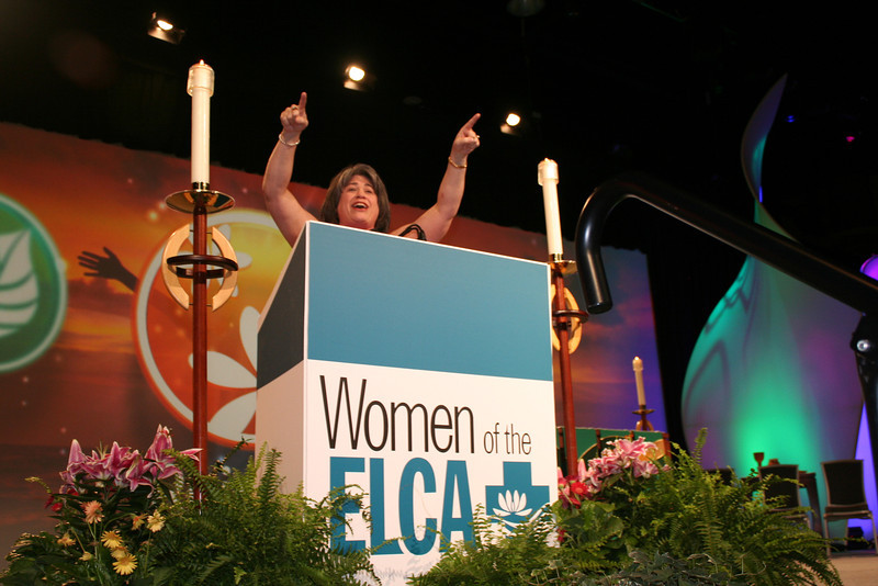 Women of the ELCA President Jennifer Michael leads the audience in cheers by region.