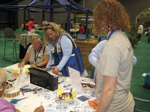 Multigenerational prayer partner exchange at Camp Cafe in the exhibit hall.