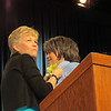 Outgoing executive board president Beth Wrenn fastens a corsage on the newly elected president.