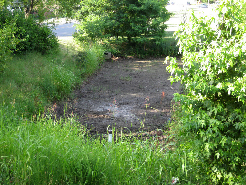 """The bioretention pond is usually dry in between rain events. The dry bed is carefully screened from recreational users by generous landscaping. The pond, which uses a sand filter system, receives drainage from 6 acres of stadium parking. Prior to the installation of this system, untreated runoff containing excess nutrients, sediment, and trace metals would rapidly flood nearby Weems Creek, and ultimately the Chesapeake Bay during storms.<br /> <br /> The Navy-Marine Corps Memorial Stadium mitigation project of 2002 embodies the holistic approach and visionary potential of Transportation Enhancements to build infrastructure that is integrated with the environment, promotes health, and provides visual amenities. The project combines a 1.25 mile multi-use trail with a series of stormwater best management practices (BMPs) as landscaping. The stadium area serves both as an athletic facility and a park-and-ride location. Now, thanks to a $590,665 TE grant and an even more substantial local match, the stadium parcel is also used on a daily basis by many walkers and cyclists. The project demonstrates an """"ecosystem approach"""" to infrastructure, where one element of the system is seamlessly interconnected with others, and performs multiple functions: preventing flooding, protecting water quality, fighting obesity, providing habitat, and serving the needs of outdoor recreation users.  Such infrastructure is characterized both by its efficiency and its livability."""