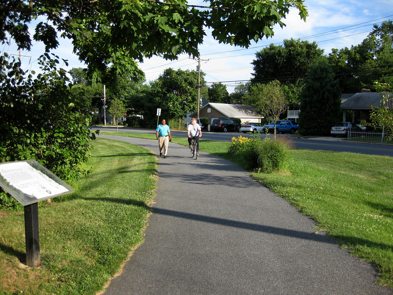 """Biorention swales along Cedar Park Road line the walking trail. In addition to receiving runoff from 18 acres of stadium/commuter parking area and Cedar Park Road itself, the swales provide a visual amenity to users of the walking trail. The wild flowers and native grasses flourishing in the swales echo with the songs of crickets, which in turn attract finches and other songbirds.<br /> <br /> The Navy-Marine Corps Memorial Stadium mitigation project of 2002 embodies the holistic approach and visionary potential of Transportation Enhancements to build infrastructure that is integrated with the environment, promotes health, and provides visual amenities. The project combines a 1.25 mile multi-use trail with a series of stormwater best management practices (BMPs) as landscaping. The stadium area serves both as an athletic facility and a park-and-ride location. Now, thanks to a $590,665 TE grant and an even more substantial local match, the stadium parcel is also used on a daily basis by many walkers and cyclists. The project demonstrates an """"ecosystem approach"""" to infrastructure, where one element of the system is seamlessly interconnected with others, and performs multiple functions: preventing flooding, protecting water quality, fighting obesity, providing habitat, and serving the needs of outdoor recreation users.  Such infrastructure is characterized both by its efficiency and its livability.<br /> <br /> Federal Award: $590,665; Local Match: $623,931; Total Cost: $1,214,596"""