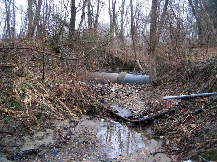 """Pre-construction conditions on Turkey Branch included exposed utilities.  These utilities are vulnerable to damage during floods and excessive weathering, as well as being unsightly.<br /> <br /> The Montgomery County Department of Environmental Protection (DEP) received a $2 million TE grant in 2000 to construct channel restoration and habitat improvements in Rock Creek Park. In an effort to restore and protect the Rock Creek watershed, which ultimately drains to the Chesapeake Bay, this project added modern stormwater controls to 730 acres to the Turkey Branch Stream subwatershed (approx. 30% of the drainage area). The project including work along 12,000 feet of the Turkey Branch Stream, along 13,400 feet of the Sycamore Creek, and along Joseph's Branch Stream. The Rock Creek watershed drains approximately 60 square miles.<br /> <br /> You can learn more about the DEP's work in this watershed by visiting their website at: <a href=""""http://www.montgomerycountymd.gov/deptmpl.asp?url=/content/dep/restoration/home.asp"""">http://www.montgomerycountymd.gov/deptmpl.asp?url=/content/dep/restoration/home.asp</a>"""
