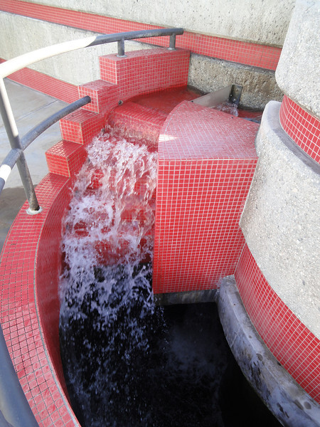 <b>The second waterfall found in the Grit Chamber, which separates grit (sediment) through centrifugal force; water enters a storage chamber below.</b>  The Santa Monica Urban Runoff Recycling Facility (SMURRF) treats and reuses dry-weather runoff from parts of western Los Angeles City and of central Santa Monica City before this source of pollution can reach Santa Monica Bay. Over 100 million gallons of urban runoff drain from Los Angeles County into the ocean on a typical dry weather day. This flow includes runoff from landscaping irrigation, car washes, hosing down of hardscapes, pool draining and other highly contaminated sources. It is the primary source of pollution into the bay, affecting beach users and aquatic life alike. SMURRF helps mitigate this pollution by treating up to 500,000 gallons daily and recycling the water for irrigation and indoor flushing purposes. In addition, the SMURRF blends technology, art, and education to create an international example of innovative urban ecological management.