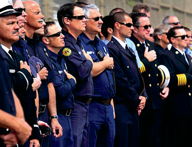 Shmuel Thaler/Sentinel Local firefighters stand tall during the singing of the National Anthem on Sunday at the commemoration at the fairgrounds.