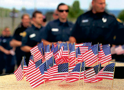 Shmuel Thaler/Sentinel Local first responders place flags in a memorial during the commemoration of September 11 at the County Fairgrounds on Sunday.