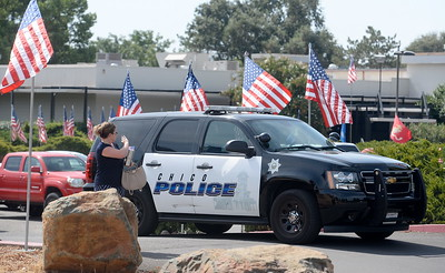 A woman waves to an officer in a Chico Police vehicle during the 9/11 memorial observance at Chico Fire Station Five on Manzanita Ave. in Chico, Calif. Monday Sept. 11, 2017. (Bill Husa -- Enterprise-Record)