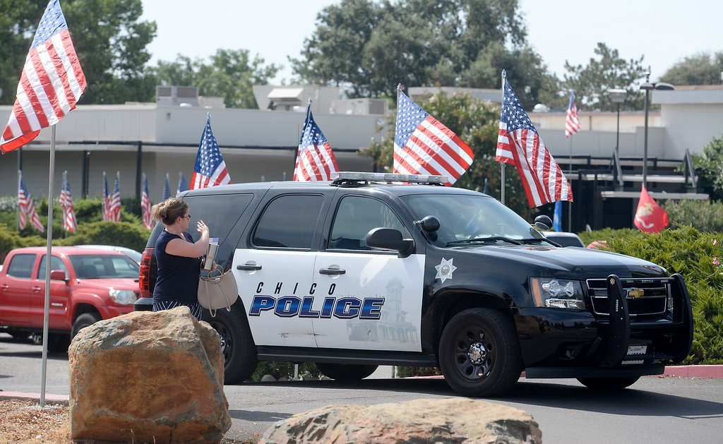 . A woman waves to an officer in a Chico Police vehicle during the 9/11 memorial observance at Chico Fire Station Five on Manzanita Ave. in Chico, Calif. Monday Sept. 11, 2017. (Bill Husa -- Enterprise-Record)