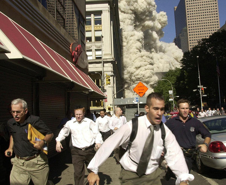FILE - In this Tuesday, Sept. 11, 2001 file photo, people run from a cloud of debris from the collapse of a World Trade Center tower in New York. (AP Photo/Suzanne Plunkett)