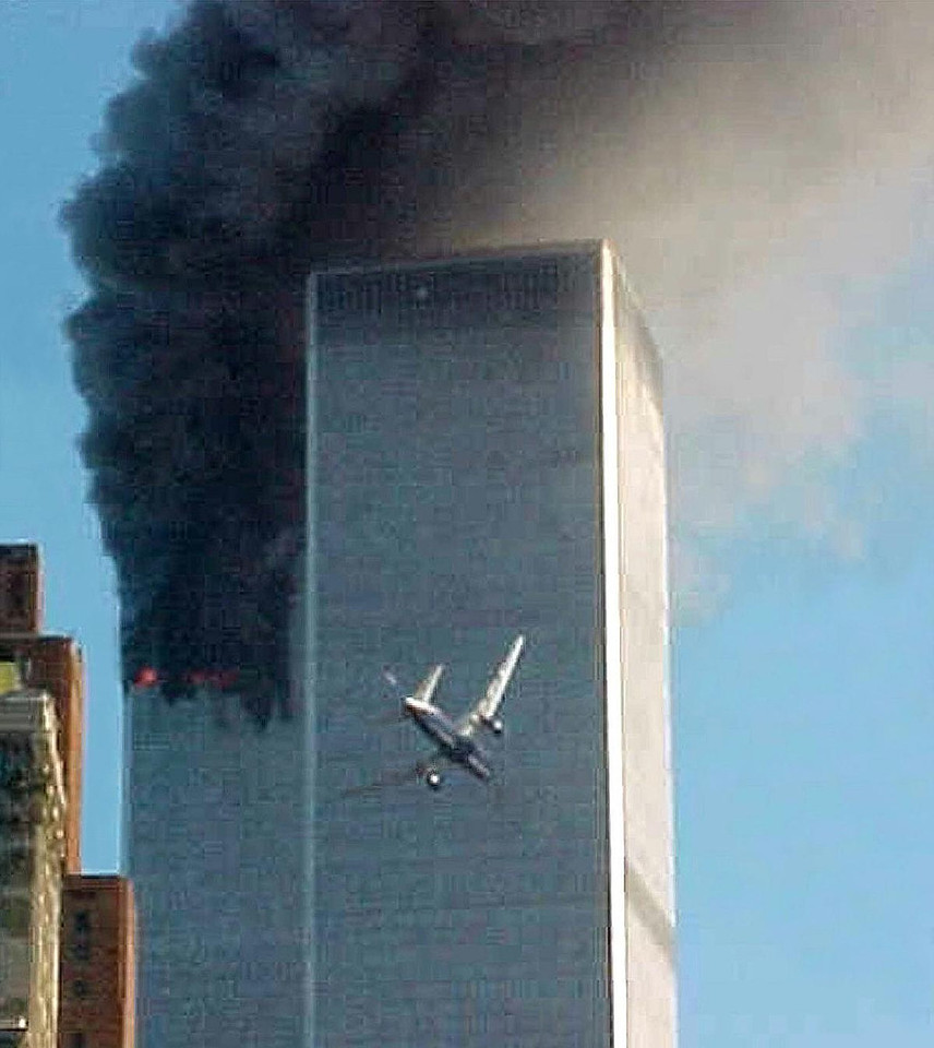 FILE - In this Sept. 11, 2001 file photo, United Airlines Flight 175 approaches the south tower of the World Trade Center in New York shortly before collision as smoke billows from the north tower. (AP Photo/Carmen Taylor)