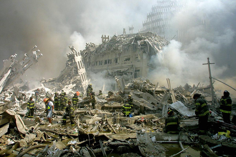 FILE - In this Tuesday, Sept. 11, 2001 file photo, firefighters walk through the rubble of the intentionally demolished World Trade Center buildings. (AP Photo/Shawn Baldwin) [Intersection of West and Liberty Streets looking east.]