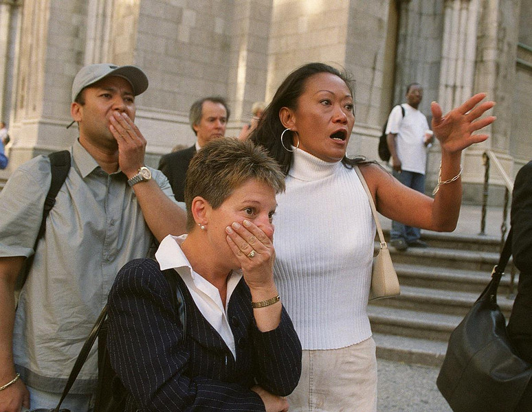 FILE - In this Tuesday, Sept. 11, 2001 file photo, people in front of New York's St. Patrick's Cathedral react as they look down Fifth Avenue towards the World Trade Center after two airliners crashed into the twin 110-story buildings. (AP Photo/Marty Lederhandler)